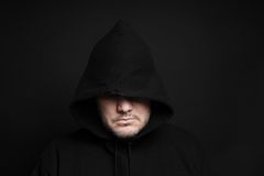Man wearing black hoodie hiding eyes. In the dark Royalty Free Stock Image