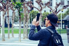 Man Wearing Black Jacket and Holding Black Android Smartphone Royalty Free Stock Photos
