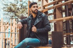Man Wearing Black Jacket and Jeans Sitting on Brown Wooden Chair royalty free stock image