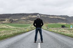 Man Wearing Black Jacket Standing on Road Near Green Grass Field during Daytime Stock Photo