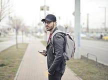 Man Wearing Black Leather Jacket Holding Smartphone stock photography