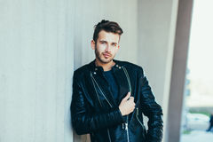 Man wearing black leather jacket. Portrait of brutal young man wearing black leather jacket and posing over urban background Royalty Free Stock Photo