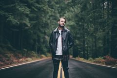 Man Wearing Black Leather Jacket Standing on Highway in the Middle of Green Trees Royalty Free Stock Image