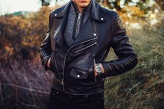 Man wearing black leather jacket and watch posing outdoors.  Royalty Free Stock Image