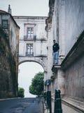 Man Wearing Black Pullover Hoodie Standing on Beside Beige Concrete Building stock images
