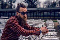 Man Wearing Black and Red Checkered Long Sleeve Shirt Wearing Black Wayfarer Sunglasses Sitting on White Wooden Chair Royalty Free Stock Photo