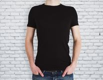 Man wearing black shirt on brick background. Man wearing empty black shirt on brick wall background. Advertisement and design concept. Mock up Stock Photos
