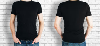 Man wearing black shirt. Man wearing empty black shirt on brick background. Front and rear view. Shopping concept. Mock up Stock Photos