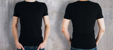 Man wearing black shirt. Man wearing empty black shirt on concrete background. Front and rear view. Shopping concept. Mock up Stock Photography