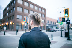 Man Wearing Black Shirt Standing on City Street during Daytime Stock Images