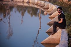 Man wearing black sunglass sitting in a place. Young man wearing black sunglass sitting around a lake unique photo royalty free stock image
