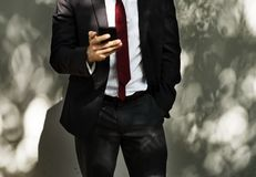 Man Wearing Black Tuxedo Holding Black Smartphone stock photography