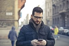 Man Wearing Black Zip Jacket Holding Smartphone Surrounded by Grey Concrete Buildings Royalty Free Stock Image