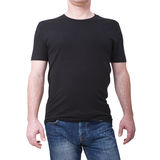 Man wearing blank black t-shirt isolated on white background with copy space. Tshirt design and people concept - close stock photography