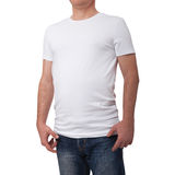 Man wearing blank blue t-shirt on gray brick wall background with copy space. Front view. Man wearing blank blue t-shirt on gray brick wall background with copy Royalty Free Stock Images