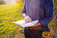 Man Wearing Blue and Black Flannel Shirt Holding White and Black Book during Daytime Royalty Free Stock Photography