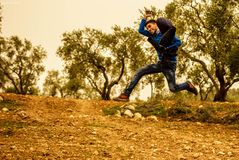 Man Wearing Blue and Black Shirt Jumping While Holding Brown Jacket Taken during Golden Hour Royalty Free Stock Images