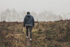 Man Wearing Blue Bubble Hoodie Jacket Walking on Green Grass Field Royalty Free Stock Image