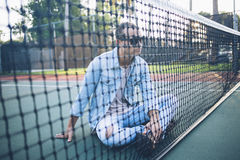 Man Wearing Blue Denim Jacket Sitting on Tennis Court Royalty Free Stock Photos