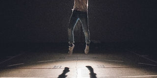 Man Wearing Blue Denim Pants and White Sneakers Jumping over Concrete Ground Stock Photo