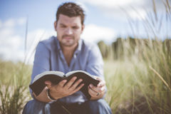 Man Wearing Blue Dress Shirt Reading Book Surrounded by Green Grass Royalty Free Stock Photography