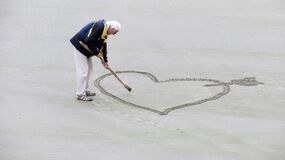 Man Wearing Blue Jacket Holding a Brown Stick Towards the Heart Drawn on Sand Stock Image