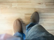 Man wearing blue jean with brown shoes on wood parquet. Top view Royalty Free Stock Photos