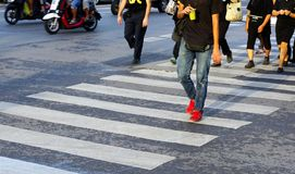 Man crossing the street crosswalk with crowd of people during rush hour, Bangkok Thailand. Royalty Free Stock Images