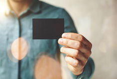 Man wearing blue jeans shirt and showing blank black business card. Blurred background. Horizontal mockup. Man wearing blue jeans shirt and showing blank black Royalty Free Stock Photo
