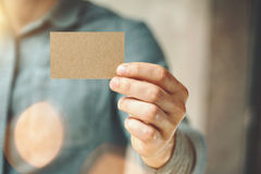 Man wearing blue jeans shirt and showing blank craft business card. Blurred background. Horizontal mockup Stock Photography