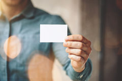 Man wearing blue jeans shirt and showing blank white business card. Blurred background. Horizontal mockup. Man wearing blue jeans shirt and showing blank white Stock Photo