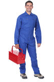Man wearing blue overalls. Holding tool kit Royalty Free Stock Image