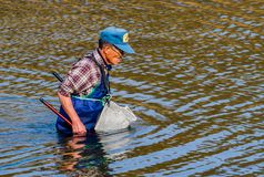 Man wearing blue waders in Kumgang river. Daejeon, South Korea-November, 14,2017: Man wearing blue waders and a basket tied to his waist fishing in Kumgang river Stock Photography