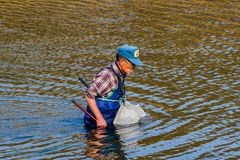 Man wearing blue waders in Kumgang river. Daejeon, South Korea-November, 14,2017: Man wearing blue waders and a basket tied to his waist fishing in Kumgang river Stock Photo