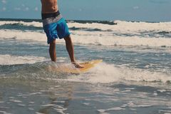 Man Wearing Blue and White Board Shorts While Surfing Stock Image