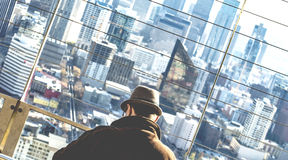 Man Wearing Brown Coat and Brown Hat on High Rise Building at Daytime Royalty Free Stock Images