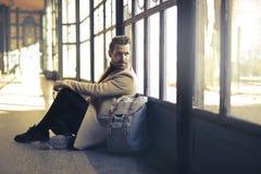 Man Wearing Brown Coat Beside White Backpack Sitting Near Window Stock Image