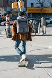 Man Wearing Brown Jacket, Blue Denim Jeans, and White Shoes Riding Skateboard on Sideway Royalty Free Stock Photos