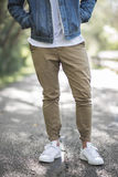 Man Wearing Brown Jeans and White Low Top Sneaker during Day Time Stock Photography
