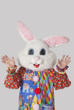 Man wearing bunny mask with standing raised hands against gray background Royalty Free Stock Photo