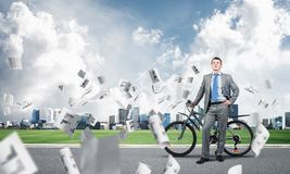 Man wearing business suit on road with bike. Man wearing business suit standing on road with bike. Businessman with bicycle under falling paper documents stock photos
