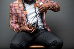 Man Wearing Button-up Shirt Holding Black and Brown Camera While Sitting on Chair stock image