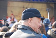 Man Wearing Cap And Grey Coat Surrounded With People Stock Photos
