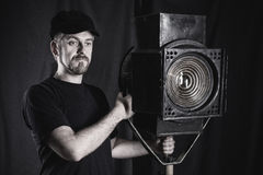 Man wearing a cap stands near stage spotlight. Royalty Free Stock Photos