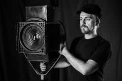 Man wearing a cap stands near stage spotlight. Stock Photos