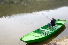 Man Wearing Cap And Vest Sitting In Green Rowboat And Fishing On The River Royalty Free Stock Image