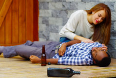 Man wearing casual clothes lying drunk passed out on wooden surface, pretty woman sitting beside him trying to get Royalty Free Stock Photos