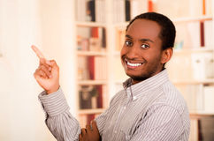 Man wearing casual clothes posing happily for camera, index finger pointing upwards, bookshelves background Royalty Free Stock Photos