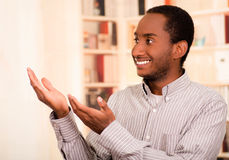 Man wearing casual clothes posing happily for camera, interacting using hands, bookshelves background Stock Images