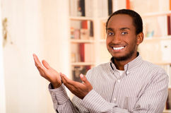 Man wearing casual clothes posing happily for camera, interacting using hands, bookshelves background Stock Image